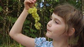 Το ευτυχές κορίτσι στο μπλε τρώει το γλυκό σταφύλι απόθεμα βίντεο