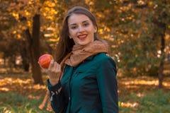 Το ευτυχές κορίτσι στο πάρκο κρατά τη Apple διαθέσιμη Στοκ φωτογραφία με δικαίωμα ελεύθερης χρήσης