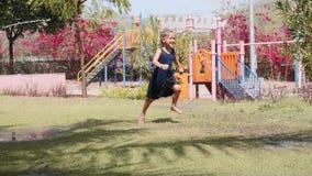 Το ευτυχές κορίτσι τρέχει κάτω από την προβολή ύδατος στο χορτοτάπητα στην παιδική χαρά παιδιών απόθεμα βίντεο