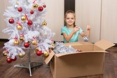 Το ευτυχές κορίτσι Χριστουγέννων βάζει τη σφαίρα στο κιβώτιο Στοκ Εικόνες