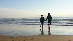 Το ευτυχές κορίτσι δύο έτρεξε χαρωπά στην παραλία, και τρεπόμενος σε φυγή πίσω απόθεμα βίντεο