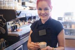 Το ευτυχές κορίτσι Barista δίνει τον καφέ στους πελάτες στοκ εικόνες