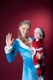 Το ευτυχές κορίτσι mom-χιονιού κρατά μωρό-Santa Claus Στοκ Φωτογραφίες