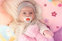 Το ευτυχές κοριτσάκι που βρίσκονται στο παχνί του με το soother και το ροζ αντέχουν στοκ φωτογραφίες