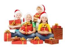 Το ευτυχές κράτημα παιδιών Χριστουγέννων παρουσιάζει Αρωγοί Santa με τα δώρα Στοκ φωτογραφία με δικαίωμα ελεύθερης χρήσης