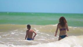 Το ευτυχές μαυρισμένο παιδί που κολυμπά και που πηδά ευτυχώς με το mom στα κύματα θάλασσας τη θερινή ηλιόλουστη ημέρα στην τροπικ απόθεμα βίντεο