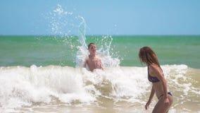 Το ευτυχές μαυρισμένο παιδί που κολυμπά και που πηδά ευτυχώς με το mom στα κύματα θάλασσας τη θερινή ηλιόλουστη ημέρα στην τροπικ φιλμ μικρού μήκους