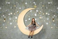 Το ευτυχές μικρό κορίτσι κάθεται σε ένα κίτρινο φεγγάρι γλυκό ονείρων Στοκ Εικόνα
