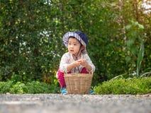 Το ευτυχές μικρό κορίτσι κρατά το καλάθι στο αγρόκτημα Καλλιέργεια & Childre στοκ εικόνα