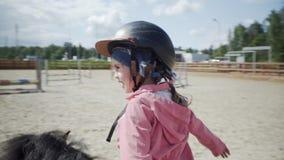 Το ευτυχές μικρό κορίτσι οδηγά ένα μαύρο πόνι στην ιππική λέσχη απόθεμα βίντεο
