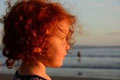 Το ευτυχές μικρό κορίτσι ομορφιάς θαυμάζει το ηλιοβασίλεμα πέρα από τη θάλασσα στην παραλία Στοκ Εικόνες