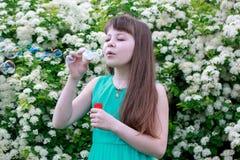Το ευτυχές μικρό κορίτσι παίζει με τις φυσαλίδες σαπουνιών Στοκ Εικόνα