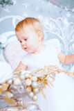Το ευτυχές μικρό κορίτσι στο άσπρο φόρεμα διακοσμεί το δέντρο στο διακοσμημένο Χριστούγεννα δωμάτιο Στοκ Φωτογραφίες