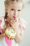 Το ευτυχές μικρό κορίτσι τρώει γλυκό doughnut στοκ φωτογραφίες