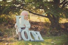 Το ευτυχές μικρό κορίτσι φθινοπώρου έχει το παιχνίδι διασκέδασης με τα πεσμένα χρυσά φύλλα Στοκ Εικόνες