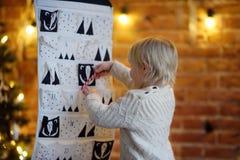 Το ευτυχές μικρό παιδί παίρνει το γλυκό από το ημερολόγιο εμφάνισης στη Παραμονή Χριστουγέννων στοκ φωτογραφίες με δικαίωμα ελεύθερης χρήσης