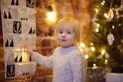 Το ευτυχές μικρό παιδί παίρνει το γλυκό από το ημερολόγιο εμφάνισης στη Παραμονή Χριστουγέννων στοκ εικόνα