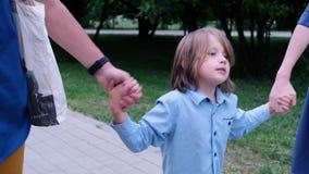 Το ευτυχές μικρό παιδί που περπατά και που κρατά τα χέρια γονέων του, κλείνει επάνω απόθεμα βίντεο