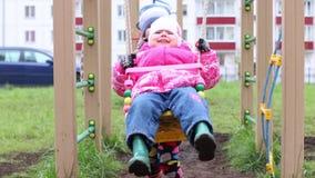 Το ευτυχές μικρό παιδί ταλαντεύεται τη μικρή αδελφή του στην παιδική χαρά απόθεμα βίντεο