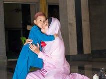 το ευτυχές μουσουλμανικό παιδί με το πλήρες φόρεμα φιλά τη μητέρα του στοκ φωτογραφία με δικαίωμα ελεύθερης χρήσης