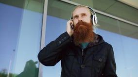 Το ευτυχές νέο γενειοφόρο άτομο hipster με τα ακουστικά και το smartphone ακούνε τη μουσική και το χορό στην οδό πόλεων Στοκ εικόνες με δικαίωμα ελεύθερης χρήσης