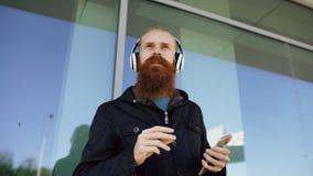 Το ευτυχές νέο γενειοφόρο άτομο hipster με τα ακουστικά και το smartphone ακούνε τη μουσική και το χορό στην οδό πόλεων Στοκ Φωτογραφίες
