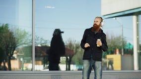 Το ευτυχές νέο γενειοφόρο άτομο hipster με τα ακουστικά και το smartphone ακούνε τη μουσική και το χορό στην οδό πόλεων Στοκ Εικόνα