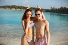 Το ευτυχές νέο ζεύγος έχει τη διασκέδαση και χαλαρώνει στην παραλία Τοποθέτηση ανδρών και γυναικών για τη φωτογραφία και τον ανόη Στοκ εικόνες με δικαίωμα ελεύθερης χρήσης