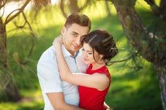 Το ευτυχές νέο ζεύγος αγκαλιάζει στο πάρκο Στοκ φωτογραφία με δικαίωμα ελεύθερης χρήσης