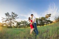 Το ευτυχές νέο ζεύγος αγκαλιάζει στο πάρκο Στοκ Φωτογραφία