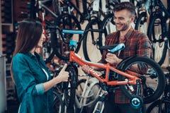 Το ευτυχές νέο ζεύγος επιλέγει το ποδήλατο παιδιών στο κατάστημα στοκ φωτογραφία με δικαίωμα ελεύθερης χρήσης