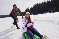 Το ευτυχές νέο ζεύγος που έχει τη διασκέδαση σε φρέσκο παρουσιάζει στις χειμερινές διακοπές Στοκ Φωτογραφίες