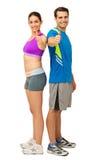 Το ευτυχές νέο ζεύγος στην αθλητική ένδυση Gesturing φυλλομετρεί επάνω στοκ φωτογραφία