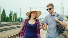 Το ευτυχές νέο ζεύγος των τουριστών με ένα smartphone πηγαίνει στο σταθμό τρένου Έννοια: σε απευθείας σύνδεση εισιτήρια διαταγής φιλμ μικρού μήκους