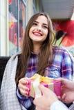 Το ευτυχές νέο κορίτσι λαμβάνει ένα δώρο από το άτομό της Στοκ Εικόνα