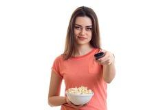 Το ευτυχές νέο κορίτσι μεταστρέφει τον τηλεχειρισμό και την εκμετάλλευση ένα πιάτο με pop-corn Στοκ Φωτογραφίες