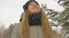 Το ευτυχές νέο κορίτσι με το χειμώνα ντύνει το φυσώντας χιόνι από το χειμερινό υπόβαθρο χεριών απόθεμα βίντεο