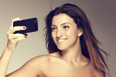Το ευτυχές νέο κορίτσι παίρνει τις εικόνες με το smartphone του Στοκ Φωτογραφία