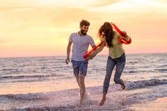 Το ευτυχές νέο ρομαντικό ζεύγος ερωτευμένο έχει τη διασκέδαση στην όμορφη παραλία στην όμορφη θερινή ημέρα Στοκ Φωτογραφία