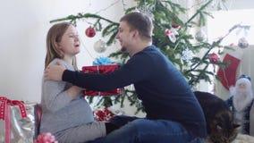 Το ευτυχές νέο όμορφο ζεύγος κάθεται κοντά στο όμορφο διακοσμημένο χριστουγεννιάτικο δέντρο Ο σύζυγος δίνει ένα κιβώτιο δώρων στη φιλμ μικρού μήκους