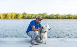 Το ευτυχές νέο lankan άτομο sri με την λευκό σκυλιών η συνεδρίαση από τον ποταμό Στοκ Εικόνα
