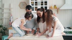 Το ευτυχές οικογενειακό μαγείρεμα στην κουζίνα, μητέρα προετοιμάζει τη ζύμη για το ψήσιμο, σε αργή κίνηση φιλμ μικρού μήκους