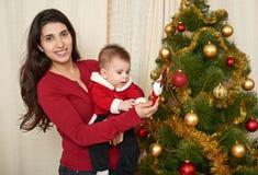Το ευτυχές οικογενειακό πορτρέτο στη διακόσμηση Χριστουγέννων, έννοια χειμερινών διακοπών, διακόσμησε το δέντρο έλατου και τα δώρ Στοκ Εικόνα