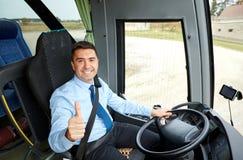 Το ευτυχές οδηγώντας λεωφορείο οδηγών και το χιόνι φυλλομετρούν επάνω στοκ εικόνα