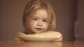 Το ευτυχές παιδί έχει ένα χαριτωμένο παιδί προγευμάτων που τρώει το πρόγευμα στο σπίτι Το παιδί στην κουζίνα στην επιτραπέζια κατ φιλμ μικρού μήκους