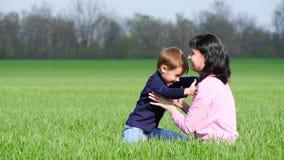 Το ευτυχές παιδί και mom παίζει στην πράσινη χλόη στο πάρκο, το αγκάλιασμα και το φιλί απόθεμα βίντεο