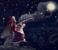 Το ευτυχές παιδί με το σκυλί εξετάζει τον ουρανό στοκ εικόνες