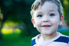 Το ευτυχές παιδί, μικρό παιδί είναι έκπληκτο και χαμογελώντας ευρέως υπαίθρια διαστημικό κείμενό σας Αναδρομικός που τονίζεται Κα στοκ φωτογραφία με δικαίωμα ελεύθερης χρήσης
