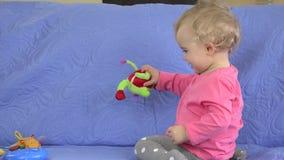 Το ευτυχές παιδί, χαριτωμένο ξανθό κορίτσι μικρών παιδιών έχει το παιχνίδι διασκέδασης με τα παιχνίδια ή τον παιδικό σταθμό απόθεμα βίντεο