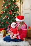 Το ευτυχές παιχνίδι αγοράκι και μητέρων κοντά στο δέντρο στα καπέλα santa γιορτάζει τα Χριστούγεννα Νέες διακοπές έτους ` s Στοκ Εικόνες